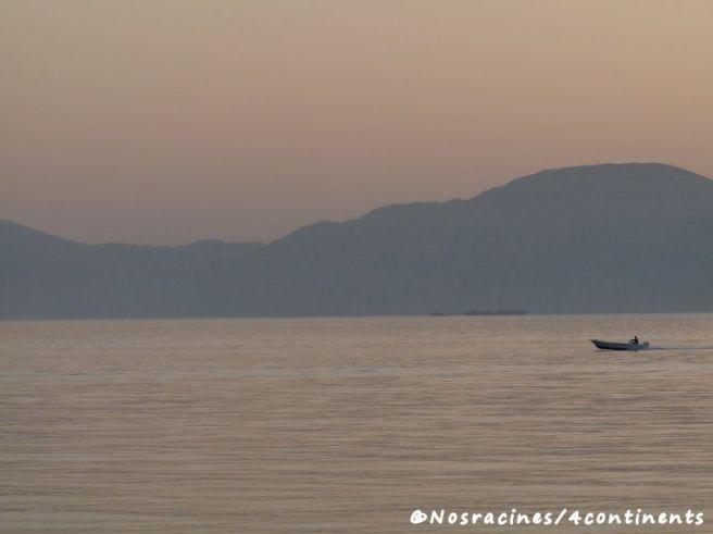 Le soleil se lève sur la mer, quelques pêcheurs sont déjà à l'œuvre